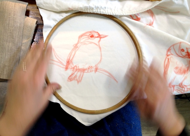 Juliet stretches the fabric into an embroidery hoop.