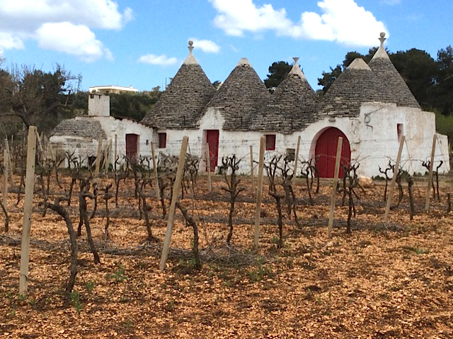 trullo with red doors and grapevines